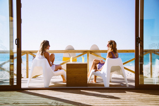 Friends Relaxing On Wooden Deck By Beach