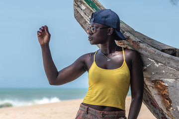 African woman with sunglasses and a backwards blue cap leaning against an old fishing boat in Cape coast Ghana West Africa.