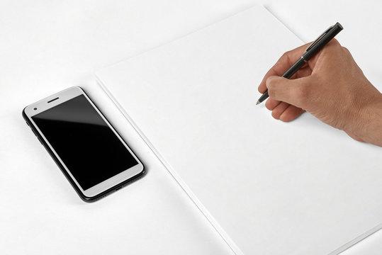 Leeres Blatt, Block, Schreibblock auf dem Tisch mit Handy, Smart Phone, Hand schreibt mit Stift Notizen auf dem Block, viel Platz Copy Space