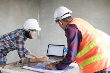Engineer and worker planning for construction building and renovate in working site Fotobehang