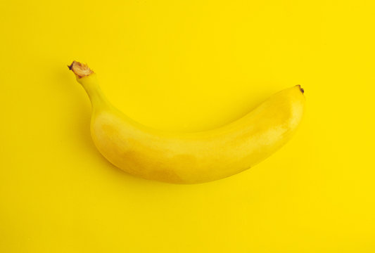 One ripe and fresh banana isolated on the yellow background