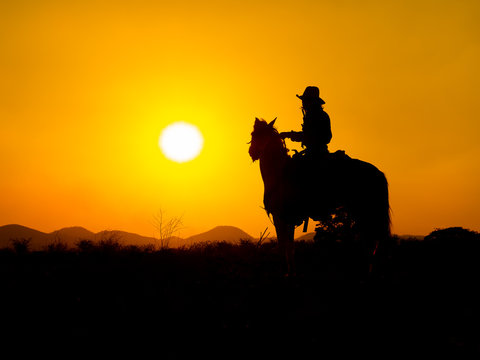 Western cowboys are sitting on horseback under the sun and preparing to use guns to protect themselves in a land that is not yet legal