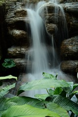 Spoed Fotobehang Bos rivier Mesmerizing vertical picture of a waterfall flowing splashing to the rocks