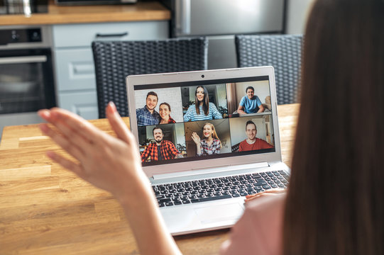 Video call, zoom. Icons of a group of people on laptop screen, app for video online communication. A woman is waving hello in webcam, back view