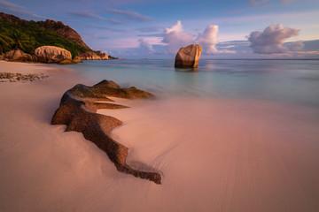 Granite rocks on tropical beach in soft sunset light