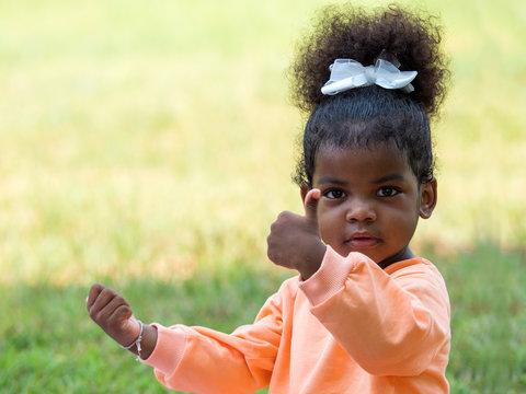 Cute dark skinned girl dancing, playing in the park. African toddler child showing thumbs up with blurry grass as copy space.