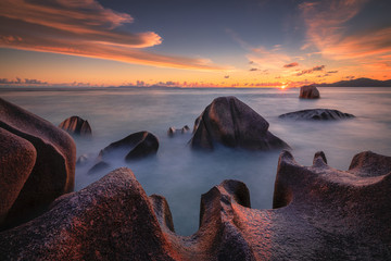 Beautiful colourful sunset on the beach with granite rocks in Seychelles.