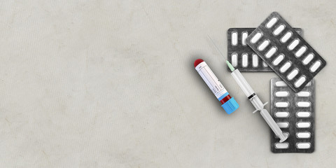 pills, syringe and blood test tube on concrete background