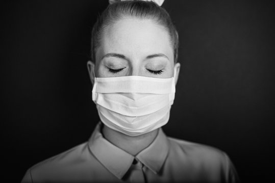 Young European woman wearing face mask with closed eyes to protect from COVID-19 isolated on black background