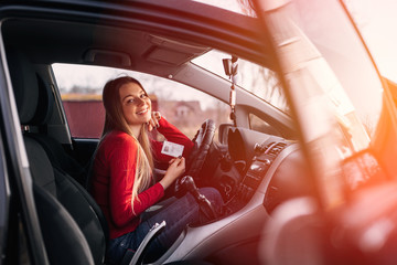Portrait of a beautiful young woman sits in car with driver's license
