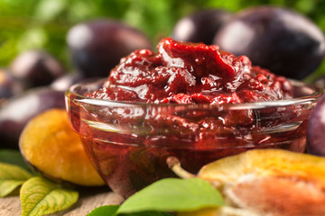 Jam of healthy organically grown plums with plum fruits on a wooden table