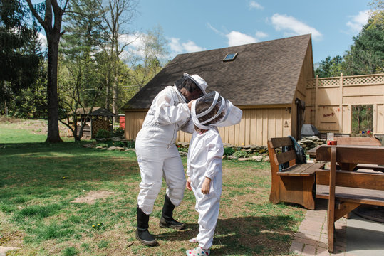 mother helping little girl getting dressed in apiarist suit to check on beehive