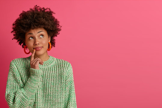 Dreamy dark skinned young woman thinks about career opportunities, stands thoughtful, concentrated upwards, dressed in knitted sweater, isolated on pink background, copy space for your promotion