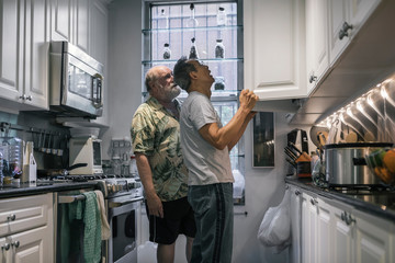 Retired Senior Gay Couple Sorting Grocery from Paper Bags in White Kitchen Cabinets