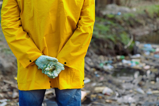 Person folding hands behind back and looking at plastic pollution