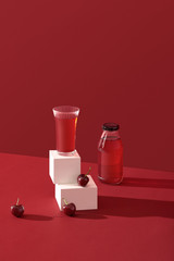A glass of cherry juice and cherry fruit