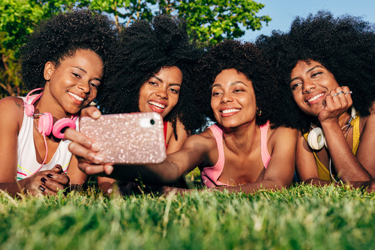 Afro women friends hanging out in the park using a cellphone