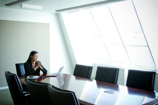 Thoughtful businesswoman sitting in conference room