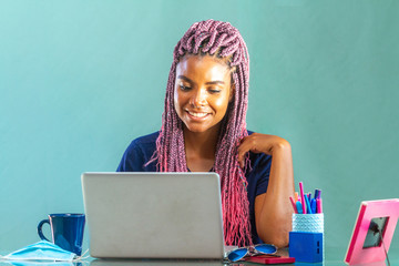 Black young woman in her home office wearing pink braids working on notebook