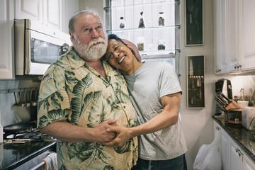Portrait of Loving Senior Gay Couple in their Kitchen