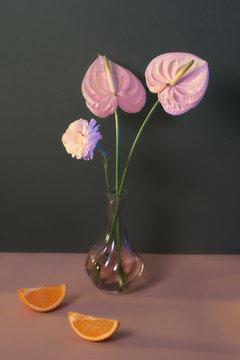 Pink flower vase and orange wedges on table