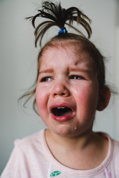 Crying Toddler Girl with Funny Topknot
