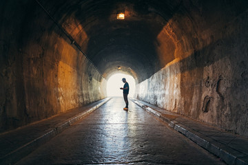 Silhouette of man addicted to the phone in a dark tunnel Fotomurales
