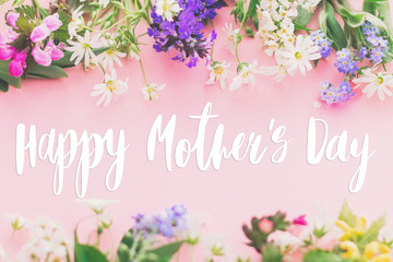 Happy Mother's day text on colorful blooming spring flowers frame flat lay on pink background. Floral greeting card. Happy Mothers day concept.