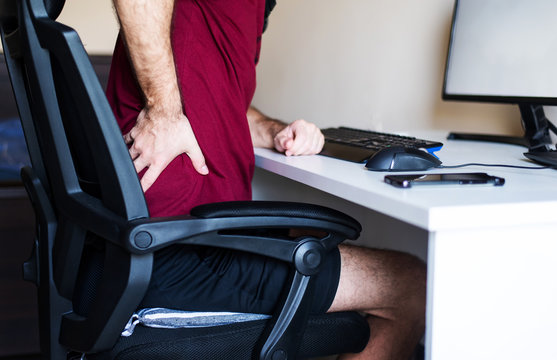 Man having back pain while working from home in an improvised office