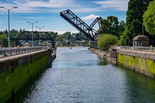 A train trestle draw bridge opens to let a tall ship pass under at the Ballard Locks in Seattle, Washington.