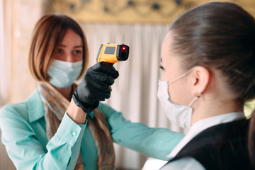The Manager of a restaurant or hotel checks the body temperature of the staff with a thermal imaging device.