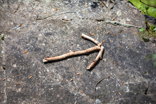 wooden stick arrow at forest mossy rock. Nature wayfinding concept woodlands play background