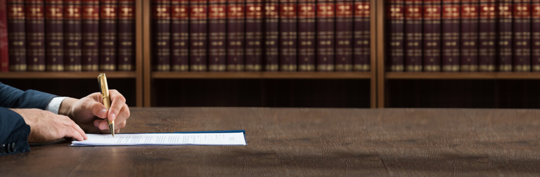 Lawyer Writing On Legal Documents At Desk