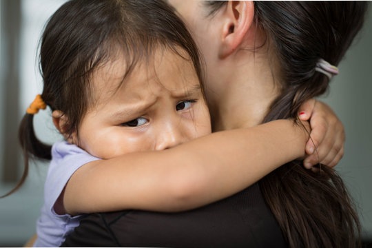 A sad child holding her mother for comfort and safety.