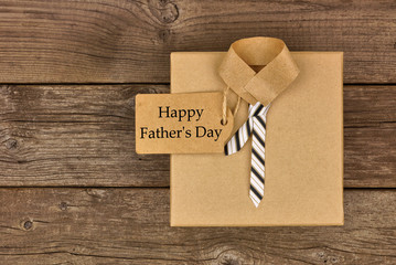 Happy Fathers Day card with shirt and tie gift box on a rustic wood background. Top view.