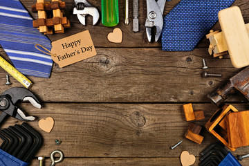 Happy Fathers Day gift tag with frame of gifts, ties and tools on a rustic wood background. Overhead view with copy space.