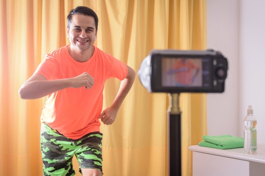 man dancing Zumba online audience. Influencer broadcasting dance class. happy young man working from home. Healthy lifestyle Video blog concept.COVID-19.Social distancing concept.