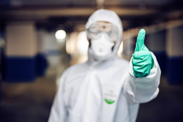 Closeup of man in sterile protective suit and mask showing thumbs up. He just disinfected whole...