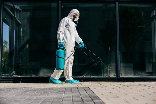 Man in sterile protective suit sterilizing outdoors from corona virus/ covid-19.