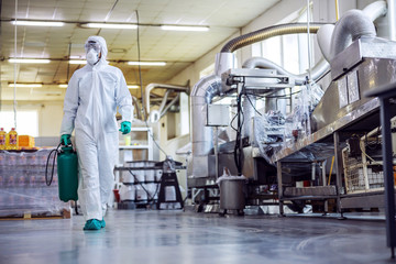 Man in protective suit and mask disinfecting food factory full of food products from corona virus / covid-19.