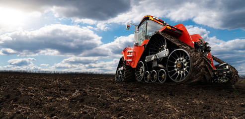 Etiqueta Engomada - Rubber tracked agricultural tractor on a field.