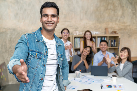 Young indian businessman and team smile, look and give handshake to camera at office in concept warm welcome and support for new comer, deal merger and acquisition business, career and job workforce.
