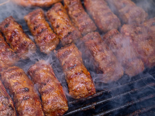 Fototapete - minced meat rolls or mici cooking on barbecue traditional romanain balkan ottoman dish 1st of may labor day celebration