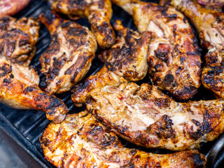 Fototapete - delicious chicken legs cooking on grill close up photo