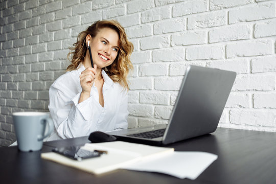 Happy freelancer woman sitting at table with laptop.