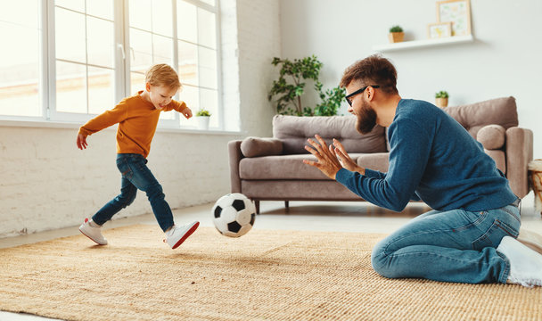 Father teaching son to play football
