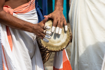A person playing an instrument called Timila which is made of polished jackwood and held together by leather brazes. It is one of the five musical instrument in Panchavadyam .
