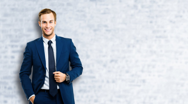 Portrait of happy confident businessman in blue suit and tie, standing against white brick wall background. Business success concept. Smiling man at studio picture. Copy space for some text or slogan.