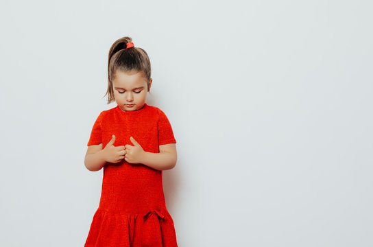 shy child girl in a red dress looks bottom. girl posing in studio