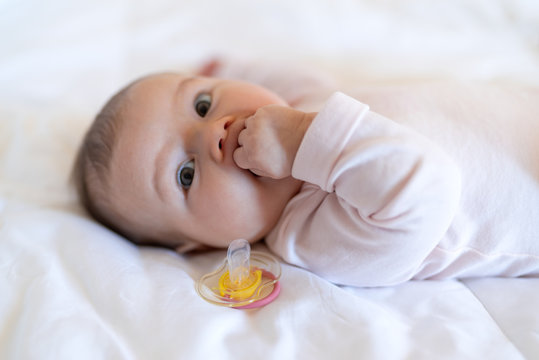 The close-up of baby girl in bed sucking fist